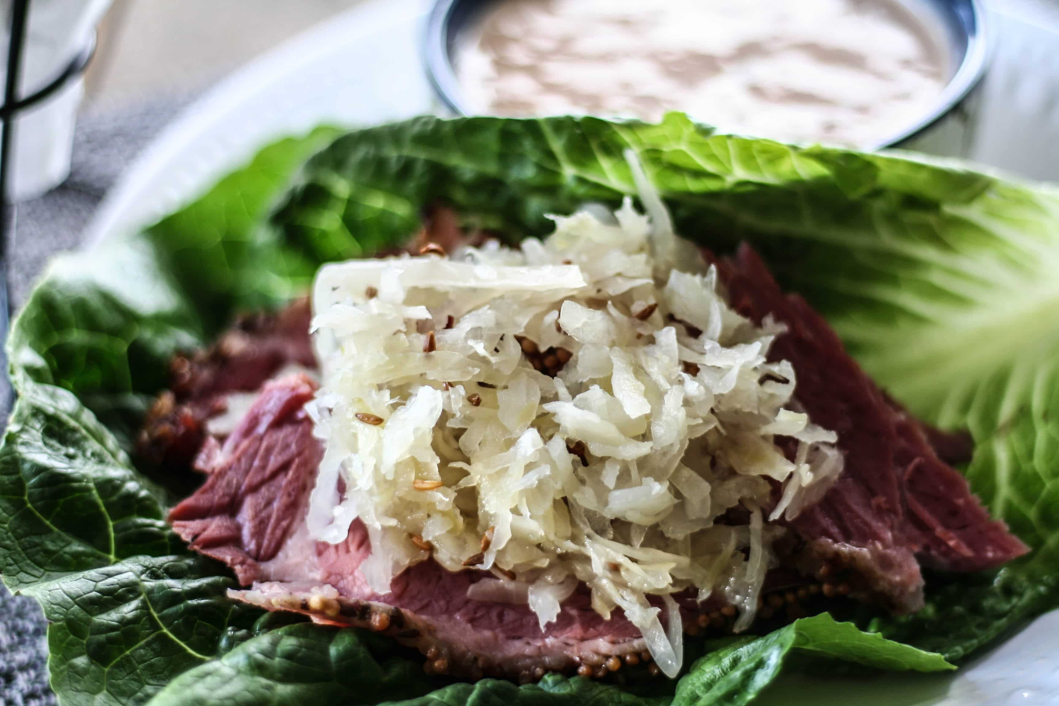 a Paleo Reuben lettuce wrap on a plate with a side dish of paleo thousand island dressing